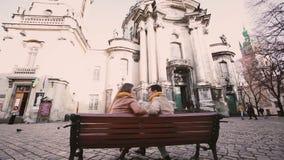 Το νέο ζεύγος κάθεται στον πάγκο και τη συζήτηση στην πόλη φθινοπώρου απόθεμα βίντεο
