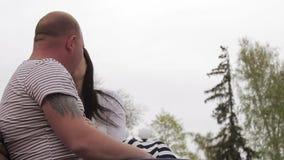 Το νέο ζεύγος κάθεται στον πάγκο και τη συζήτηση στο βράδυ στο πάρκο πόλεων απόθεμα βίντεο