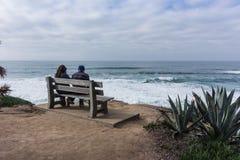 Το νέο ζεύγος κάθεται στον πάγκο κοιτάζοντας έξω πέρα από τον ωκεανό Στοκ Φωτογραφία