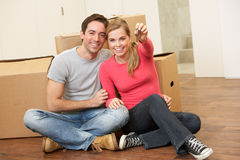 Το νέο ζεύγος κάθεται στο πάτωμα κρατώντας βασικό διαθέσιμο Στοκ εικόνα με δικαίωμα ελεύθερης χρήσης