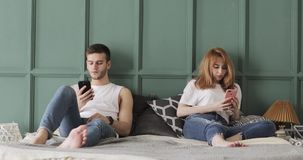 Το νέο ζεύγος κοιτάζει βιαστικά smartphones στο κρεβάτι τους στο σπίτι απόθεμα βίντεο