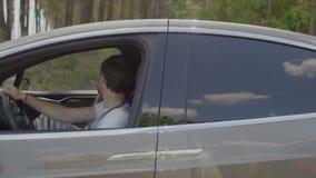 Το νέο ζεύγος μιλά κατά τη διάρκεια της οδήγησης στο σύγχρονο αυτοκίνητο κοντά στο δάσος απόθεμα βίντεο