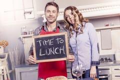 Το νέο ζεύγος παρουσιάζει έναν πίνακα με την πρόσκληση γευμάτων Στοκ εικόνα με δικαίωμα ελεύθερης χρήσης
