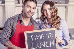 Το νέο ζεύγος παρουσιάζει έναν πίνακα με την πρόσκληση γευμάτων Στοκ φωτογραφία με δικαίωμα ελεύθερης χρήσης