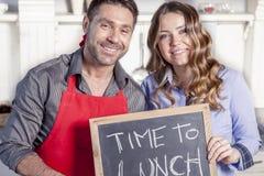 Το νέο ζεύγος παρουσιάζει έναν πίνακα με την πρόσκληση γευμάτων Στοκ Φωτογραφίες