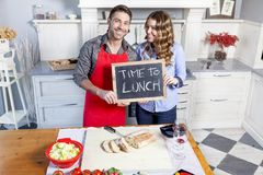 Το νέο ζεύγος παρουσιάζει έναν πίνακα με την πρόσκληση γευμάτων Στοκ Φωτογραφία