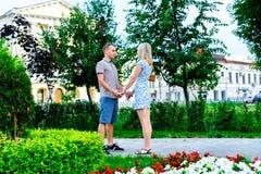 Το νέο ζεύγος που στέκεται στην εκμετάλλευση κορδελλών πάρκων το ένα το άλλο χέρια ` s, μια δήλωση της αγάπης, εξευγενίζει το αγκ Στοκ εικόνες με δικαίωμα ελεύθερης χρήσης