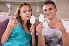 Το νέο ζεύγος που τρώει το παγωτό και που δίνει φυλλομετρεί επάνω στοκ φωτογραφία με δικαίωμα ελεύθερης χρήσης