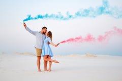 Το νέο ζεύγος που φιλά και που κρατά το χρωματισμένο καπνό στα χέρια, ρομαντικό ζεύγος με το μπλε χρώμα και το κόκκινο χρώμα καπν Στοκ φωτογραφία με δικαίωμα ελεύθερης χρήσης