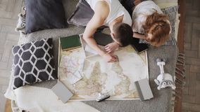 Το νέο ζεύγος προγραμματίζει τις διακοπές που συζητούν και που δείχνουν τις θέσεις για την επίσκεψη σε έναν χάρτη χρησιμοποιώντας φιλμ μικρού μήκους
