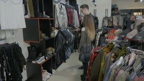 Το νέο ζεύγος σπουδαστών που περπατά τα ενδύματα αποθηκεύει τη λεωφόρο ψάχνοντας το σωστό ζευγάρι των παπουτσιών και της μπλούζας απόθεμα βίντεο