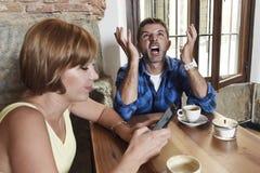Το νέο ζεύγος στη καφετερία με Διαδίκτυο και το κινητό τηλέφωνο εθίζουν τη γυναίκα που αγνοεί το ματαιωμένο άνδρα Στοκ φωτογραφία με δικαίωμα ελεύθερης χρήσης