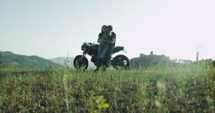 Το νέο ζεύγος στη μοτοσικλέτα σταμάτησε στην καταπληκτική θέση με την όμορφη άποψη και την απόλαυση τοπίων του χρόνου από κοινού φιλμ μικρού μήκους