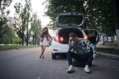Το νέο ζεύγος στο δρόμο έχει τα προβλήματα με το αυτοκίνητο Στοκ φωτογραφία με δικαίωμα ελεύθερης χρήσης
