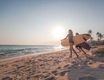 Το νέο ζεύγος των ευτυχών surfers χαμόγελου τρέχει με τις ιστιοσανίδες στην ωκεάνια ακτή, αθλητικός ενεργός τρόπος ζωής στοκ εικόνες με δικαίωμα ελεύθερης χρήσης