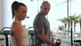 Το νέο ζεύγος των bodybuilders εκπαιδεύει τα bicepses τους στη γυμναστική πολυτέλειας sportspeople απόθεμα βίντεο