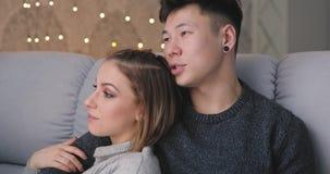 Το νέο ζεύγος χαλαρώνει το αγκάλιασμα ομιλίας μαζί στο σπίτι φιλμ μικρού μήκους