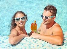 Το νέο ζεύγος χαλαρώνει στην πισίνα Στοκ Φωτογραφία