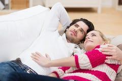 Το νέο ζεύγος χαλαρώνει σε κάθε άλλοι οπλίζει σε έναν καναπέ Στοκ Φωτογραφίες