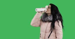 Το νέο θηλυκό πρότυπο σε ένα χειμερινό παλτό πίνει το τσάι από μια άσπρη θερμο κούπα απόθεμα βίντεο