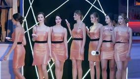 Το νέο θηλυκό στα λαμπρά φορέματα κοκτέιλ με τις συσκευές στα χέρια πηγαίνει στη σειρά στο σκηνικό του μαύρου φωτισμένου τοίχου απόθεμα βίντεο