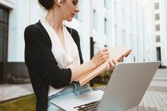 Το νέο θηλυκό freelancer που κάνει την έρευνα αγορών εργασίας για το σύγχρονο lap-top, κάθεται επάνω υπαίθρια στην αστική οδό στοκ εικόνα με δικαίωμα ελεύθερης χρήσης