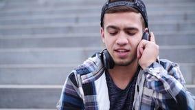 Το νέο καθιερώνον τη μόδα άτομο ακούει τη μουσική στη συνεδρίαση smartphone στα βήματα υπαίθρια απόθεμα βίντεο