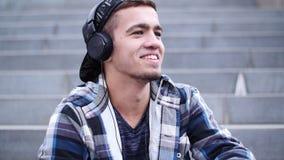 Το νέο καθιερώνον τη μόδα άτομο ακούει τη μουσική στη συνεδρίαση smartphone στα βήματα υπαίθρια φιλμ μικρού μήκους