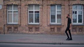 Το νέο καθιερώνον τη μόδα γενειοφόρο άτομο περπατά κατά μήκος της οδού κοντά στο κτήριο τούβλου στην πόλη απόθεμα βίντεο