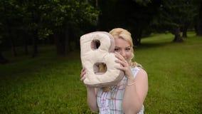Το νέο καλό κορίτσι έχει τη διασκέδαση σε ένα πάρκο το καλοκαίρι Τοποθέτηση γυναικών με το γράμμα Β μαξιλαριών απόθεμα βίντεο