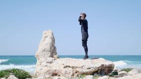 Το νέο κατάλληλο καυκάσιο άτομο που στέκεται στο μεγάλο βράχο στην παραλία βάζει τα γυαλιά ηλίου του επάνω και αρχίζει να τρέχει  απόθεμα βίντεο