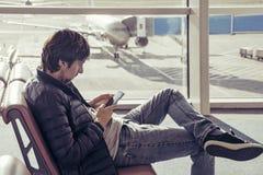 Το νέο καυκάσιο άτομο στα τζιν και outerwear κάθεται στην αίθουσα αναμονής αερολιμένων καρεκλών και χρησιμοποίηση του smartphone Στοκ Εικόνες
