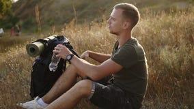 Το νέο καυκάσιο άτομο, ταξιδιώτης που βγάζει το σακίδιο πλάτης του στο έδαφος και κάθεται στη χλόη τηγανητών για να πάρει ένα υπό απόθεμα βίντεο