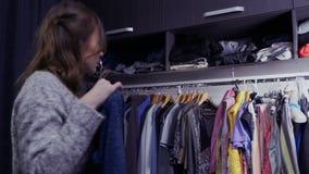 Το νέο καυκάσιο κορίτσι επιλέγει τα ενδύματα στο βεστιάριο στο σπίτι απόθεμα βίντεο