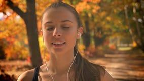 Το νέο καυκάσιο κορίτσι με τα ακουστικά γυρίζει στη κάμερα και χαμογελά στο φθινοπωρινό υπόβαθρο απόθεμα βίντεο