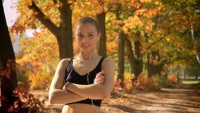 Το νέο καυκάσιο κορίτσι στο jumpsuit με τα όπλα διέσχισε την τοποθέτηση στη κάμερα και το χαμόγελο απόθεμα βίντεο