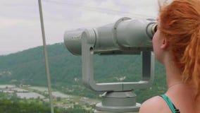 Το νέο καυκάσιο ξανθό κορίτσι στην εξέταση της πλατφόρμας εξετάζει τα βουνά μέσω των διοπτρών απόθεμα βίντεο