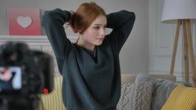 Το νέο κοκκινομάλλες κορίτσι blogger, χαμόγελο, που μιλά στη κάμερα, γίνεται ένα hairstyle, βόστρυχος, εγχώρια άνεση απόθεμα βίντεο