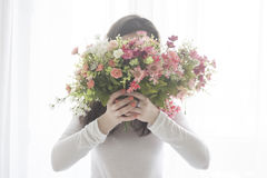 Το νέο κορίτσι έκλεισε το πρόσωπο με μια ανθοδέσμη των λουλουδιών, που απομονώθηκε στο άσπρο υπόβαθρο Στοκ Φωτογραφία