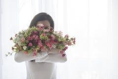 Το νέο κορίτσι έκλεισε το πρόσωπο με μια ανθοδέσμη των λουλουδιών, που απομονώθηκε στο λευκό, διάστημα κειμένων Στοκ Εικόνες