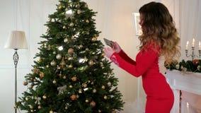 Το νέο κορίτσι έτους σε ένα εορταστικό φόρεμα φωτογραφίζει το χριστουγεννιάτικο δέντρο, μοιράζεται τις φωτογραφίες μέσω του Διαδι απόθεμα βίντεο