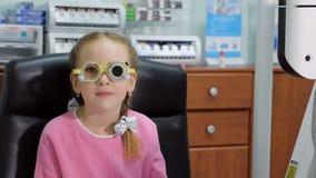 Το νέο κορίτσι έχει την εξέταση οφθαλμών που εκτελείται από τον οπτικό, optometrist ή το γιατρό ματιών φιλμ μικρού μήκους