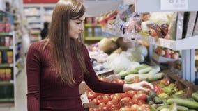 Το νέο κορίτσι αγοράζει τα λαχανικά στο τμήμα παντοπωλείων υπεραγοράς και τα βάζει στη πλαστική τσάντα απόθεμα βίντεο