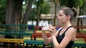 Το νέο κορίτσι αθλητικού αθλητισμού εκτελεί μια προθέρμανση των χεριών στον αθλητικό τομέα στο πάρκο φιλμ μικρού μήκους