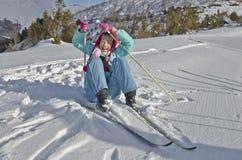 Το νέο κορίτσι ανακτεί με τη διασκέδαση μετά από την πτώση κατά κάνοντας σκι Στοκ Εικόνα