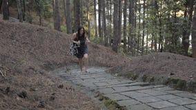 Το νέο κορίτσι αναρριχείται επάνω στο δασικό περπάτημα πολύ που κουράζεται και πίνει το νερό απόθεμα βίντεο
