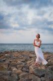 Το νέο κορίτσι δαπάνες στις άσπρες φορεμάτων σε μια αποβάθρα πετρών ενάντια στο θόριο Στοκ φωτογραφίες με δικαίωμα ελεύθερης χρήσης
