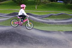 Το νέο κορίτσι απελευθερώνει το ποδήλατο στο οδοιπορικό εμποδίων Στοκ εικόνα με δικαίωμα ελεύθερης χρήσης