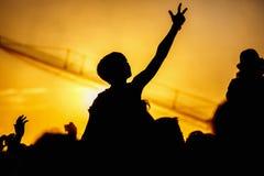 Το νέο κορίτσι απολαμβάνει μια συναυλία βράχου, σκιαγραφία στο ηλιοβασίλεμα Στοκ Εικόνα
