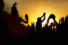 Το νέο κορίτσι απολαμβάνει μια συναυλία βράχου, σκιαγραφία στο ηλιοβασίλεμα Στοκ Φωτογραφία